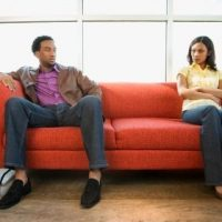 Couple sitting on couch in conflict